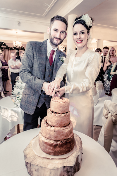 Winter wedding,  Vintage wedding, reception room, donington manor, bride and groom cutting pork pie wedding cake, mark pugh photography