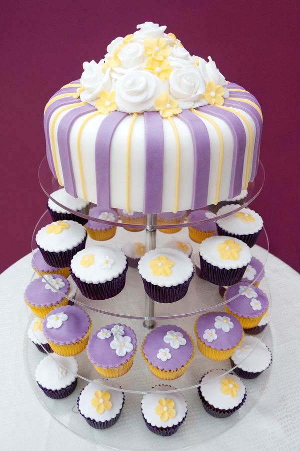 Purple And Yellow Cake With Cupcakes Underneath Portrait