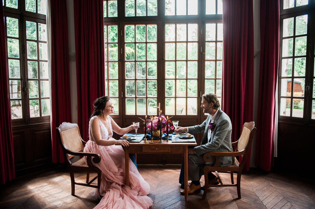 Dark Fairytale inspired Wedding - Wit Photography - pink wedding dress - Unielle Couture - bride and groom at tabele